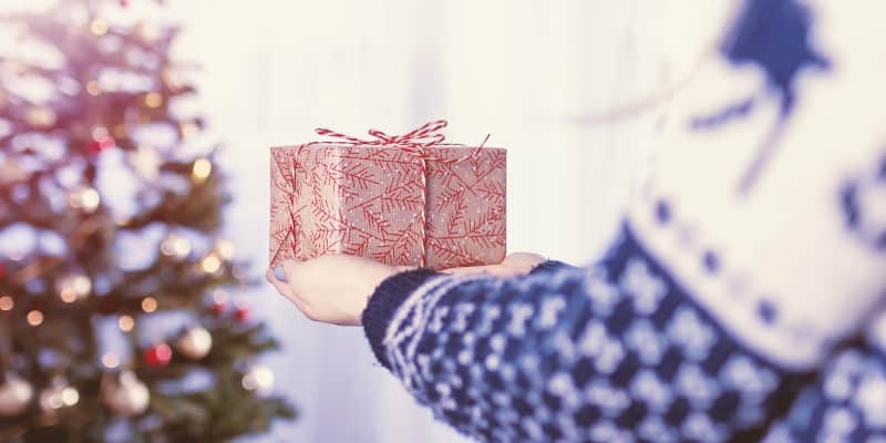 Person holding present next to Christmas tree