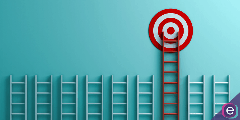 Ladders on a light blue wall with a target above one