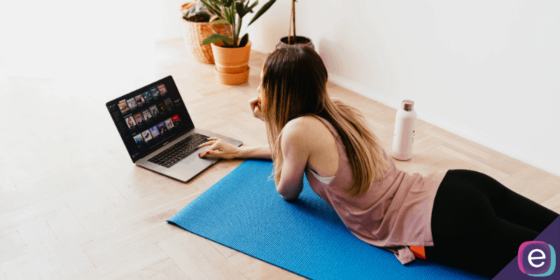 Girl choosing music laying on yoga mat